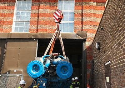 Pic showing the 1st Industrial team outside of the location using a high outdoor crane to finalise the generator plant move.